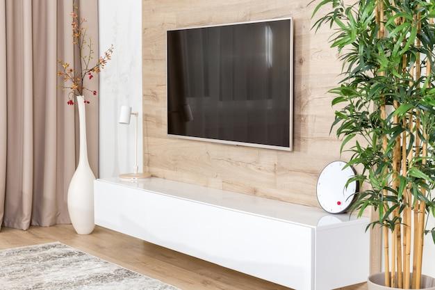 Sala de estar com sofá e tv led na parede de madeira