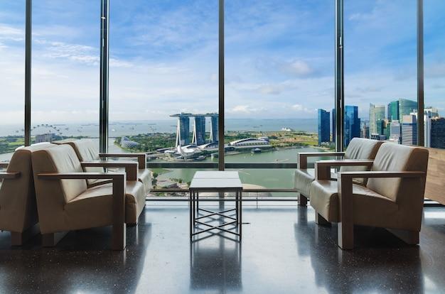 Sala de estar do hotel de luxo com as janelas que negligenciam a cidade em singapura.