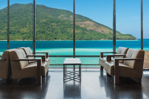 Sala de estar do hotel de luxo com as janelas que negligenciam o mar em phuket, tailândia.