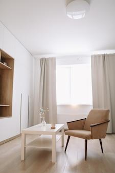 Sala de estar elegante e bem iluminada com poltrona confortável e mesa perto da janela.