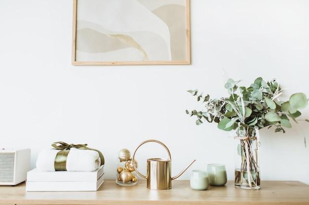 Sala de estar em estilo nórdico escandinavo com moldura para fotos na mesa de madeira de parede branca com caixa de presente e buquê de flores
