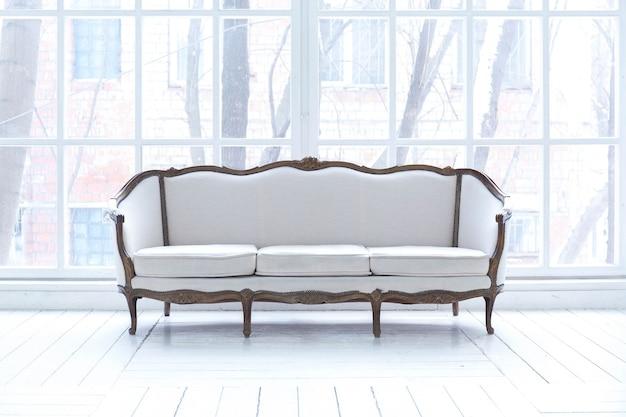 Sala de estar espaçosa e bem iluminada com design clássico elegante, decoração antiga e móveis elegantes e bonitos no estilo antigo