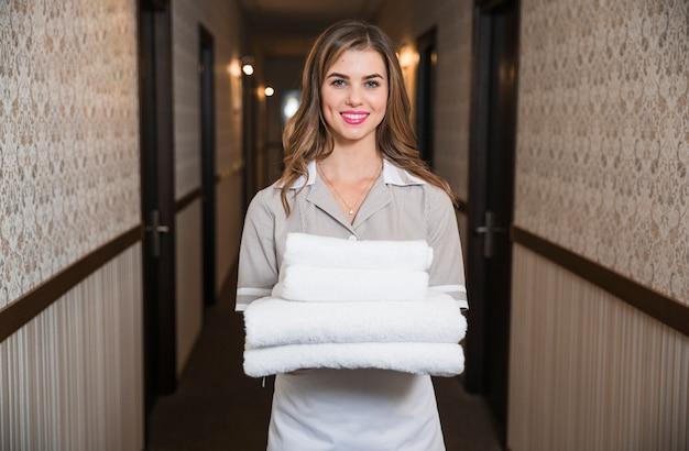 Sala de estar feliz em pé no corredor do hotel segurando toalhas lavadas