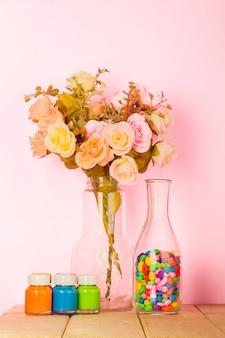 Sala de estar moderna colorida com vaso de rosas coloridas e fundo rosa pastel