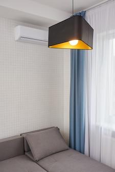 Sala de estar moderna com grande parede branca vazia e sofá cinza, sem pessoas