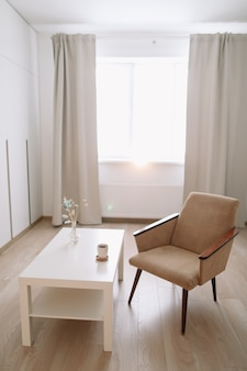 Sala de estar moderna com poltrona confortável e mesa junto à janela.