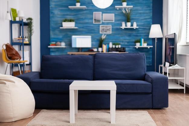 Sala de estar moderna sem ninguém com mobília e paredes azuis, lindamente decorada. decoração bastante simples do apartamento. decoração retro elegante, aconchegante.