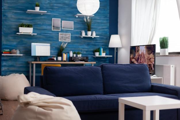 Sala de estar moderna vazia sem pessoas com sofá confortável na parede, estilo elegante com local de trabalho ao fundo e televisão. interior sem ninguém com paredes azuis, lindo apartamento decorado