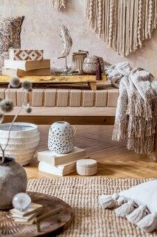 Sala de estar oriental moderna com chaise longue bege de design, lindo macramê, travesseiros, bandeja de madeira, livro, decoração e acessórios pessoais elegantes na decoração da casa.
