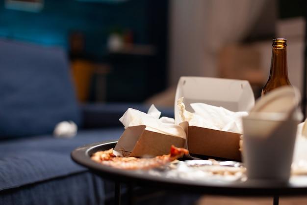 Sala de estar vazia e suja com garrafa de cerveja e guardanapos no sofá azul