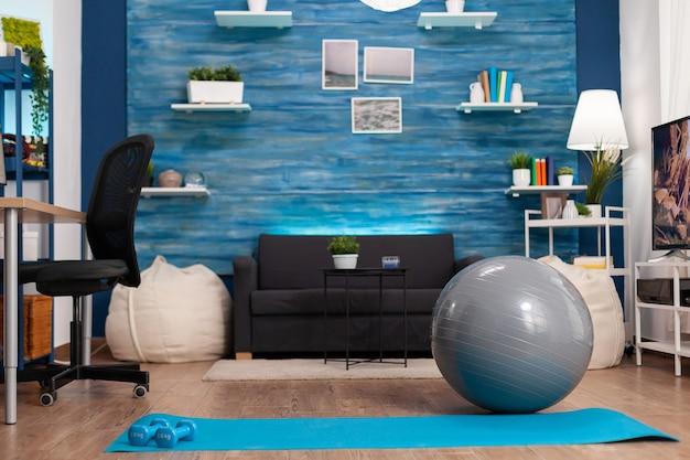 Sala de estar vazia sem ninguém pronto para o treinamento físico com tapete de ioga e halteres