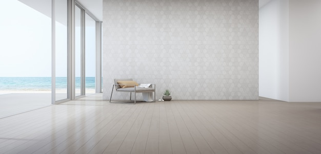 Sala de estar vista mar da casa de praia de luxo com poltrona perto da porta no piso de madeira.