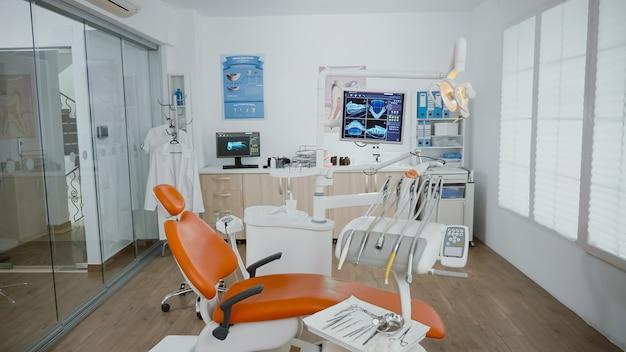 Sala de estomatologia ortodontista vazia e iluminada, sem ninguém dentro