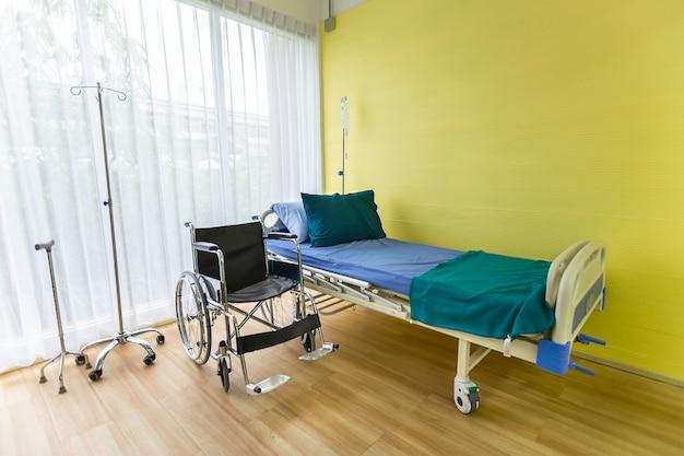 Sala de hospital com cama vazia, aparelho de infusão, líquido intravenoso e cadeiras de rodas para criação