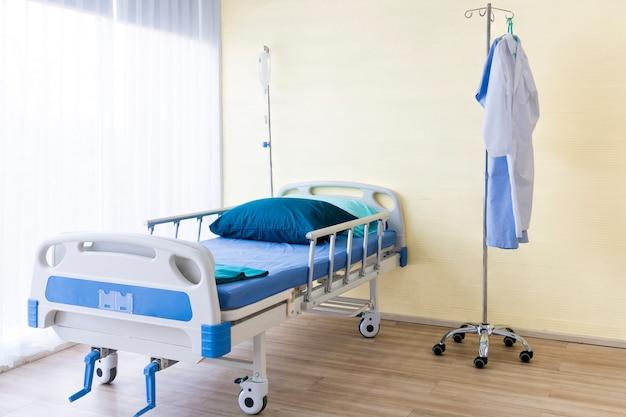 Sala de hospital com cama vazia, aparelho de infusão, líquido intravenoso e suíte médica.