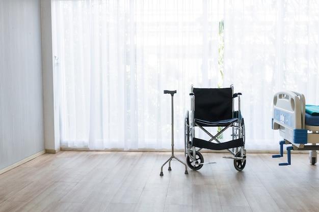 Sala de hospital com leito vazio, aparelho de infusão, líquido intravenoso e cadeiras de rodas.