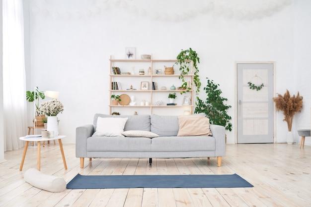 Sala de ioga com grande janela clara em apartamento branco moderno.
