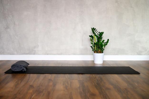 Sala de ioga com tapete preto e planta em vaso branco com piso de madeira e parede de concreto cinza