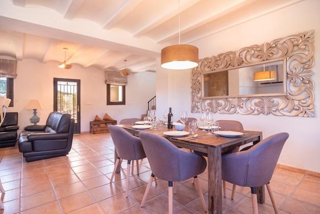 Sala de jantar com mesa e cadeiras com pratos em casa rústica