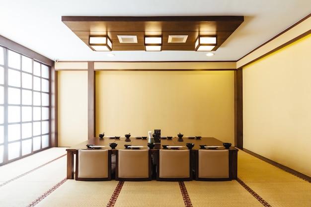 Sala de jantar de estilo japonês com mesa de madeira no centro e oito cadeiras de almofada.