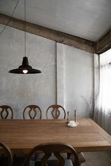 Sala de jantar moderna e elegante, com luz natural e parede de concreto com mesa e cadeiras de madeira