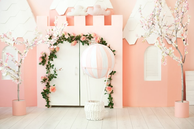 Sala de jogos com a barraca do castelo rosa para as crianças. quarto das crianças. decorações para uma festa infantil. um quarto com tenda, porta branca e balão. jardim da infância