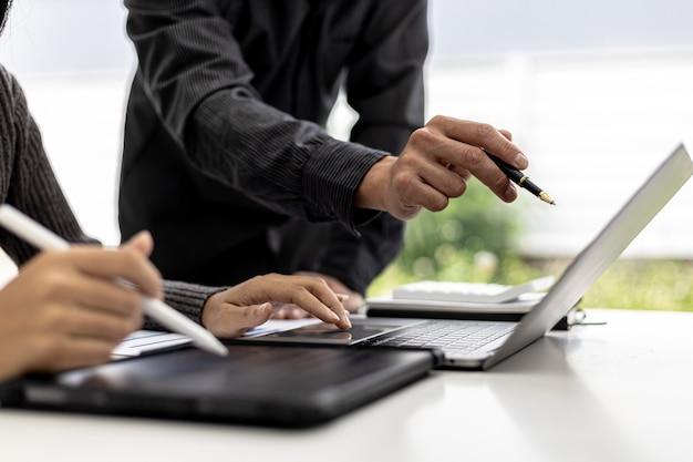 Sala de reunião de uma startup onde os empresários apontam para a tela de seus laptops para ver os resumos financeiros da empresa, eles se reúnem sobre temas financeiros mensais. conceito de gestão financeira