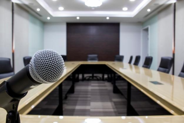 Sala de reuniões luxuosa em um corporaçõ grande microfone e sala de reuniões moderna da tabela com preto da cadeira.