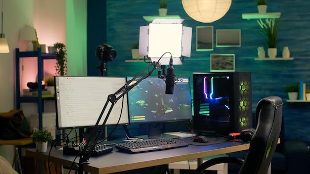 Sala de streaming vazia com computador profissional potente, teclado e mouse rgb, fones de ouvido e microfone