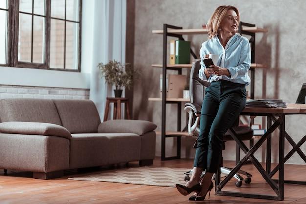 Sala de trabalho. advogada loira elegante em pé perto da mesa na sala de trabalho e bebendo chá