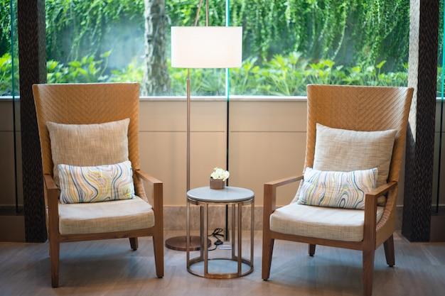 Sala de visitas interior do estilo luxuoso da tabela do lado da cadeira de madeira marrom dois