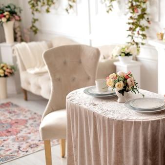 Sala decorada em estilo clássico com cadeiras antigas e mesa de centro decorada com arranjo floral