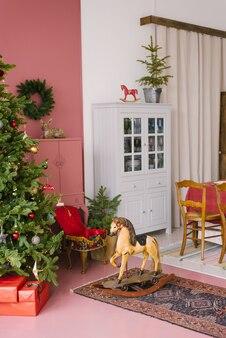 Sala decorada para o natal. brinquedo de cavalo de balanço de madeira perto da árvore de natal