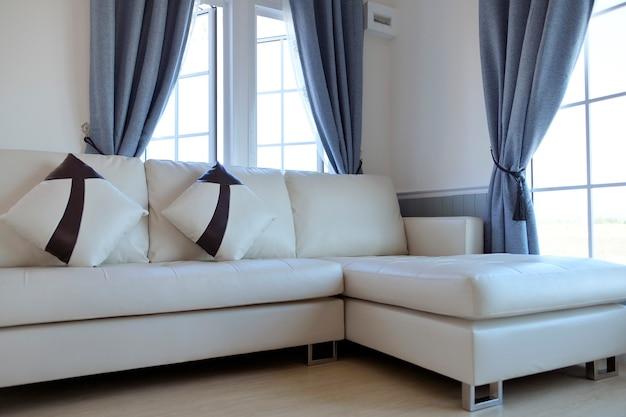 Sala dentro da casa com sofá de couro branco no meio de uma grande janela. e tem uma cortina cinza claro