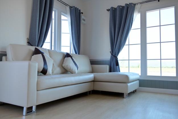 Sala dentro da casa com sofá de couro branco no meio de uma grande janela.