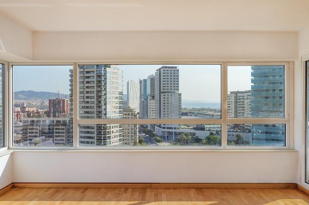 Sala ensolarada com grandes janelas pela manhã com vista panorâmica para o bairro com bu ...