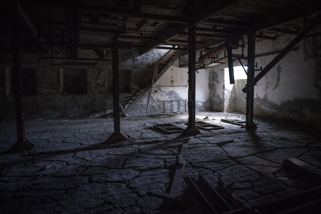 Sala industrial escura abandonada com piso rachado