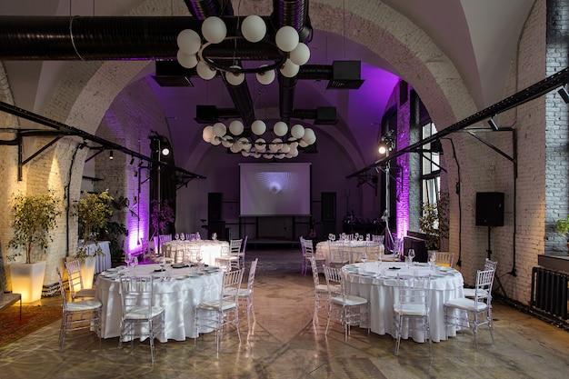Sala interna com mesas para banquete ou casamento