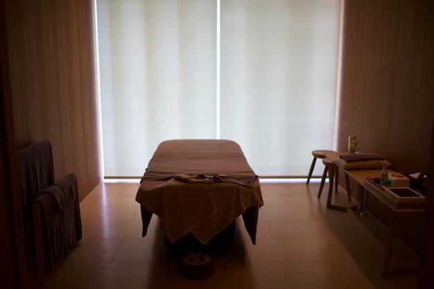 Sala para massagem corporal roupa de cama está vazia. a luz natural do sol brilha pelo contrário.