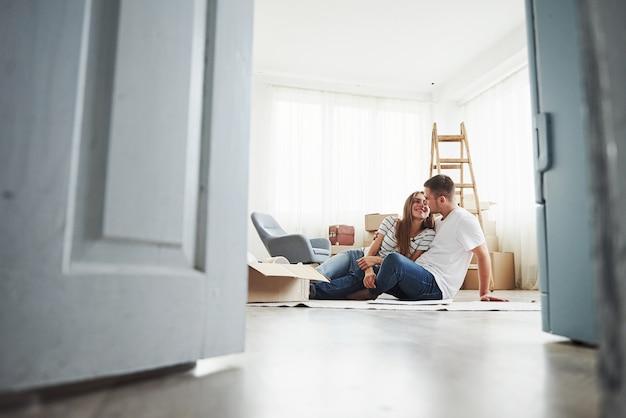 Sala vazia com caixas e escada. casal jovem alegre em seu novo apartamento. concepção de movimento.