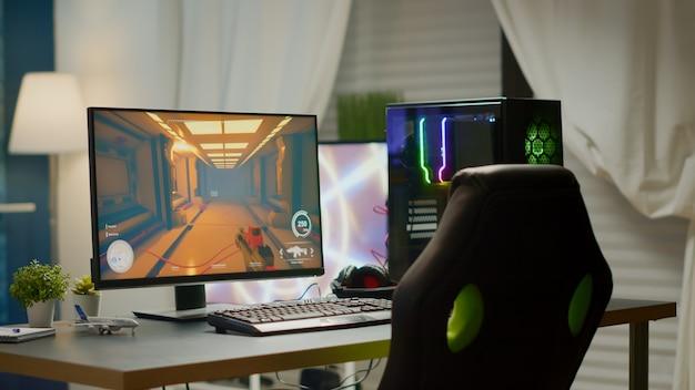 Sala vazia com computador pessoal poderoso rgb para videogames online e cadeira de jogos, jogo de tiro em primeira pessoa na tela. este quarto aconchegante com design moderno é iluminado com luz aconchegante e neon.