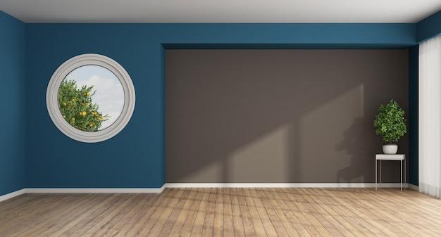Sala vazia com janela redonda na parede azul