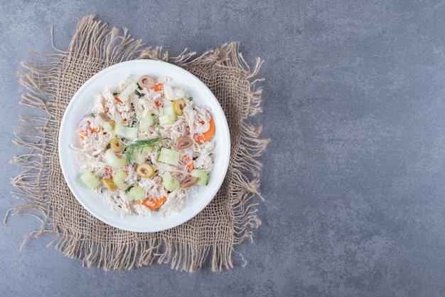 Salada apetitosa com frango no prato branco.