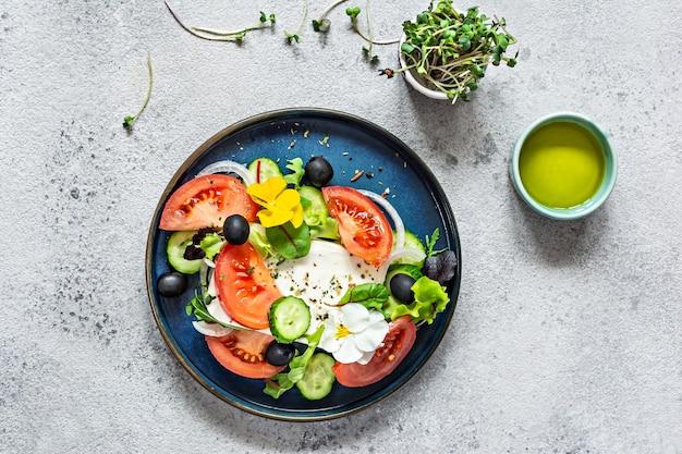 Salada apetitosa com queijo feta vegetais frescos tomates pepinos cebolas alface crocante microgreens e flores violetas porção não padronizada de salada grega comida com flores