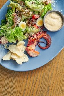 Salada apetitosa com tentáculo de polvo grelhado, ovos de codorna, alface, pão torrado e molho branco em um prato azul em uma parede de madeira. feche acima do foco seletivo