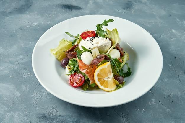 Salada apetitosa com tomate, salmão, anchovas e cream cheese em um prato branco. superfície de concreto
