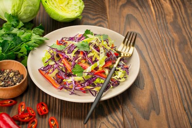 Salada brilhante de repolho roxo, repolho branco, pimentão em um prato sobre uma mesa de madeira. salada de legumes fresca. fundo de comida. prato vegetariano. vista de cima. copie o espaço.