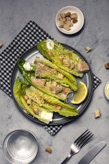 Salada caesar caseira com romanine, queijo, croutons, frango, limão e molho.