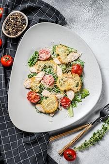 Salada caesar clássica com peito de frango grelhado, parmesão, ovos de codorna, tomate e alface romana. fundo branco. vista do topo