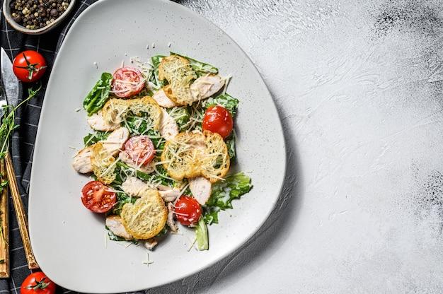 Salada caesar clássica com peito de frango grelhado, parmesão, ovos de codorna, tomate e alface romana. vista do topo. copie o espaço